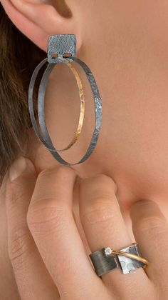 Carved Double Hoop Earrings by Heather Guidero. Two hand-fabricated and textured hoops in oxidized sterling silver and 22k bimetal swing freely from a square oxidized sterling silver post top. Lightweight and kinetic, this new take on the classic hoop earring dresses things up with the combination of black and gold.