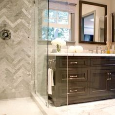shower herringbone tile- dark cabinet- glass door, solid surface mixed in