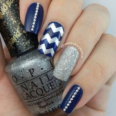 Navy blue nails with silver patterns.