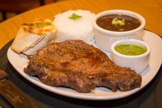 Patron's platter featuring Chuleta (Ribeye steak) with a side of Jasmine rice, Gaucho's signature beans stew, Chimi bread and Chimichurri dipping sauce.