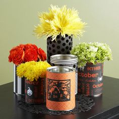 """Recycled Halloween Centerpiece Scrapbook papers and floral accents are all it takes to """"upcycle"""" yesterday's tin cans into a """"green"""" Halloween centerpiece. Standard- and economy-size tin cans work well for this craft, although the more varied the sizes, the more intriguing the display. Wrap with scrapbook paper or add die-cut scenes or stickers as desired. Would work for cutlery containers on food table"""
