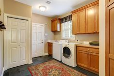 A contemporary laundry room with light wood cabinets and charcoal tile floors covered by a red and beige traditional style area rug. This laundry room contains a closet and has a door leading to the garage.