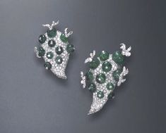 A RARE PAIR OF DIAMOND AND EMERALD CLIP BROOCHES, BY PAUL FLATO  Each pavé-set diamond plaque of freeform design, enhanced by emerald beads, accented by a diamond collet or extending single-cut diamond organic tentrils, mounted in platinum, circa 1940