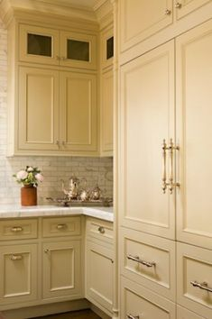 Love the color of these cabinets and the marble tile backsplash.