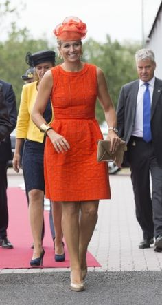 The queen wears an orange dress by Natan. Click on the image to see more looks.