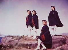 Four nurses looking out to sea. Laugarness, Iceland - June 1942. They are wearing white hospital uniforms with dark blue capes and garrison caps with maroon piping.
