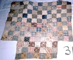 "Doll Quilt, 16.75"" x 16""; stained, fading, 1800-1849, block size: 1-1/4"", cotton fabric, hand pieced, edged turned in, no separate binding, cotton batting, hand quilted with ecru thread, tag pinned to back: ""Made by Elizabeth Gilman Age 4 1825."""