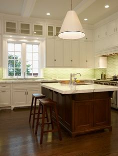 dark wood floors with a dark wood island and white cabinets with a different type of glass tiles