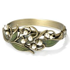A sculptured bracket of art nouveau style lilies-of-the-valley and joining leaves span across a split shank oval hinged bracelet. - Leaves are hand enameled in translucent green to emphasize texture i