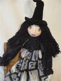 She is a sweet Halloween witch art doll that is all hand made by me. This witch measures 26 inches tall. She is dressed in black and gray colors. Her body and face are made from premium muslin fabrics. The face is all hand painted, her nose is needle sculptured. Her hair is a solid black color, made from yarn that has been all hand sewn on. This adorable witch is ready to enjoy some Halloween fun. Dressed in a black and grey dress made from high quality quilting fabrics. The dress bodice is…