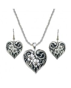angling heart earrings and necklace with two flowers and bright cut western engraving atop a black hand painted background. These earrings hang at just the right height to be noticed. Featuring a western design with two fleurettes tangled in a scrolling filigree design, this black and silver jewelry set is antiqued for an added old-world appeal.  SKU: MSLVR-JS1122