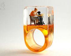 Machine à coudre - bague de couturières à la main avec une couturière minie et sa machine à coudre sur une bague orange en résine de fonte