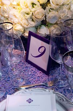 Table numbers are backed with purple paper that matches the couple's monogram and décor.
