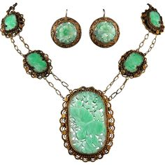 This necklace was made with 19th century clothing ornaments and a stunning carved and pierced jade plaque as the focal piece. The 4 bright apple green