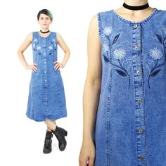 Super cute 1990s grunge denim tank dress. Features silver buttons down the front, engraved with suns! Front is embroidered with flowers in blue and