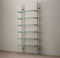 RH's 1930s French Bistro Shelving:Inspired by sleek 1930s shelving that once held dishes and glassware in a French bistro, our storage pairs adjustable glass shelves with cast brass poles that mount easily to the wall.