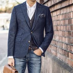 Perfect the smart casual look in a deep blue wool sport coat and navy jeans. Shop this look on Lookastic: https://lookastic.com/men/looks/blazer-cardigan-long-sleeve-shirt/21197 — White Long Sleeve Shirt — Charcoal Pocket Square — Charcoal Cardigan — Navy Wool Blazer — Brown Woven Leather Belt — Navy Jeans — Tan Leather Briefcase