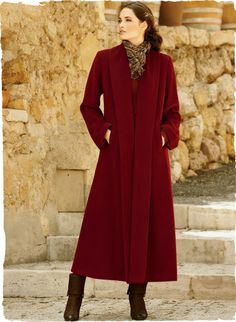 A sweeping statement in an ankle-grazing silhouette, this dramatic deep ruby red coat has a back pleat and luxuriously deep, buttonless shawl collar. In plush woven baby alpaca (72%) and wool (28%).