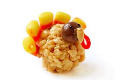 Rice krispy turkey. After mixing up the peanut butter rice krispies, and while still warm, use your hands to make small balls. Use peanut butter to stick on candy cor feathers, his whopper head, cashew beak, and string licorice waddle. Give him some eyes with black frosting. To get them to balance, squish the bottom slightly or I think they'd be cute on sucker sticks as krispy turkey pops.