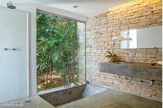Voltado para um jardim nos fundos, o banheiro ganhou bancada e banheira de concreto armado, impermeabilizado com resina poliuretânica. Projeto da arquiteta Irina Bruscky.