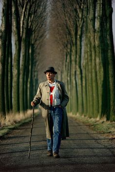 The lines lead your eyes to the man in the center of the photograph.  Joseph Beuys walks down an alley of poplar trees in the Düffel area © Gerd Ludwig