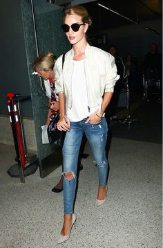 Rosie Huntington Whiteley steps out in a cropped bomber jacket, white top, distressed blue skinny jeans, pointed toe suede heels, sunglasses and a black bag.