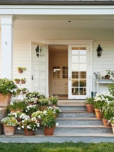 In this photo: White flowers—including salvia, violas, petunias, begonias, and lantana—adorn the side porch. like the terra cotta pots on gray porch Modern Farmhouse, Farmhouse Style, Vintage Farmhouse, White Farmhouse, American Farmhouse, Farmhouse Garden, French Farmhouse, Farmhouse Front Porches, Farmhouse Stairs