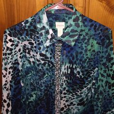 NWT Chico's Button Front Top This fabulous top/blouse from chico's is beautiful shades of teal, blues, green. It is called watercolor spots summer top LS largo teal. It looks almost like a leopard type print. Beautiful rhinestones down the entire front!!! It is a sheer material can be worn alone or with something under it. I would wear it year round. My daughter bought this for me for Xmas and it is too large unfortunately. Actually forgot I had it!! Size 1 Chico's Tops