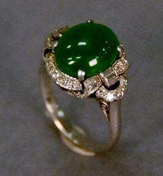 Chinese platinum ring set with oval cabochon green jade surrounded by round cut diamond and flanked by baguette diamonds, size 4 - Realized Price: $3,900.00