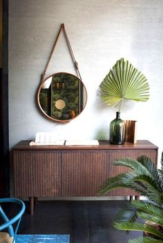 Plant leaf in vintage bottle with hanging round mirror