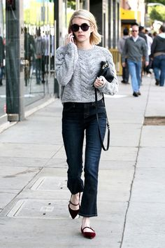 Emma Roberts wears round sunglasses with a gray crop sweater, dark blue jeans and Tabitha Simmons flats