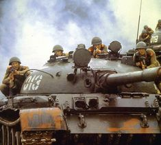 Soviet soldiers on top of a T-62 tank.