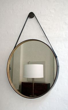 An IKEA hack perhaps? With the round mirror, some paint and a leather strap...