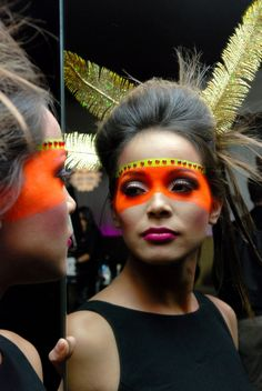 Crystals outline a vibrant orange and yellow make-up mask complete with gold feather accents.
