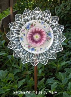 Plate flower garden whimsy  I saw these (at a craft show) made upright and used as bird feeders. Any type of old glass plate, bowl, cup, saucer, candy dish, etc. can be used and it can be stacked as high as you like!