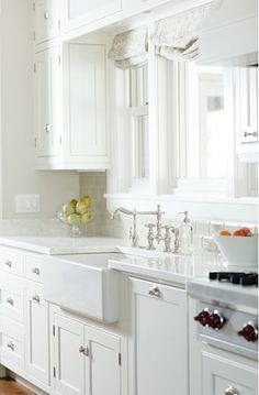 Beautiful light filled kitchen with white cabinets, white quartz countertops and polished nickel hardware. The white counters pair with gray beveled subway tile. A large farmhouse sink pairs with a polished chrome bridge faucet that sits below a wide window.