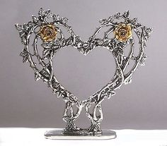 <p> Brimming with leaves and thorns, these two masterfully detailed rose vines come together in the shape of a heart. The blooming roses are pewter dipped in 23k gold. It was originally designed  as a wedding-cake topper, but it is a lovely sculpture on its own. We make this lacy-looking Pewter Cake Top by hand from lead-free pewter. It's 6 1/2%2...