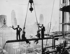 Two waiters serve two steel workers lunch, on a girder high above New York City, 14th November 1930.  Picture by Charles C. Ebbets
