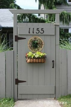 Lovely private garden gate with planter and round window