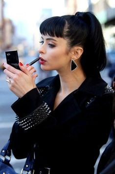 Krysten Ritter touches up her already beautiful face.  Perfect ponytail and black jacket