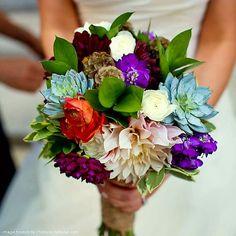 Lovely Bridal Bouquet Showcasing: Café Au Lait Dahlias, Cranberry Dahlias, Garnet Dahlias, Orange Ranunculus, White Ranunculus, Grape Purple Stock, Scabiosa Pods, Teal Succulents, Green Foliage