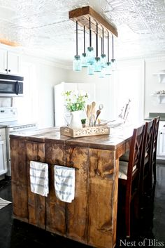 A DIY wide-plank kitchen island and matching mason-jar pendant light fixture add personal charm to this farmhouse kitchen.