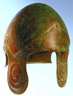 Greek Bronze Helmet: An ancient Greek helmet of the Chalcidian Type, with a carinated ridge around the top, rising to a point over the forehead, and large repoussé volutes on the rounded cheek pieces. Ca. 550-500 BC.