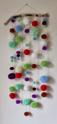 DIY Driftwood Pom Pom Wall Hanging, would love to make one for the succah, or maybe with yarn wrapped balls, a little quicker and takes less yarn....