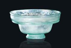 A ROMAN PALE GREEN GLASS CUP CIRCA 4TH CENTURY A.D. The body with flaring sides, short vertical rim rising from a folded hollow flanged collar, applied base ring with diagonal tooling marks 2.7/8 in. (7.4 cm.) high