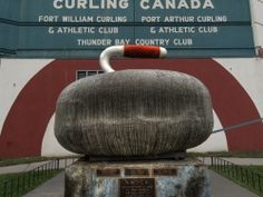 This large curling stone sits on a pedestal outside of the Fort William Gardens in Thunder Bay, Ontario. (HDR of curling stone and pedestal part of image)
