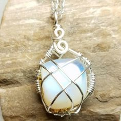 Silver non-tarnish caged opalite pendant on silver colored chain necklace.