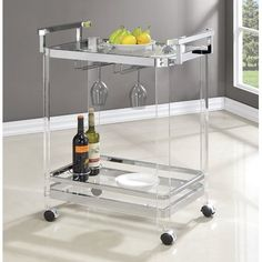 A clean-lined and cosmopolitan touch for any seating group or entertainment space, this bold and sleek bar cart brings a bit of loft-worthy and luxe appeal to your well-curated space. Featuring two tiers of oval glass shelving held up by a shimmering metal frame, this understated cart is a stylish stage for any display. Use the bottom tier to display a classic chinoiserie vase, then add a ceramic table lamp and stack of hardcover novels for a refined look in the living room. Hosting a small…