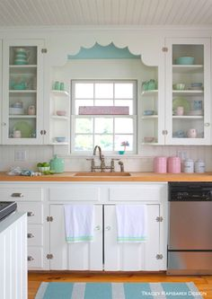Sweet Cottage Kitchen. whimsical molding over the sink, beadboard ceiling and backsplash and cabinet ends, stainless hardware, butcher block counter, pops of blue