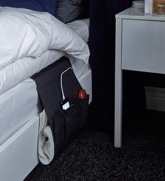 Das Bild zeigt FLÖRT Tasche für Fernbedienung in Schwarz, die hier seitlich am Bett befestigt wurde, um Platz für ein Handy und eine Zeitung zu bieten.